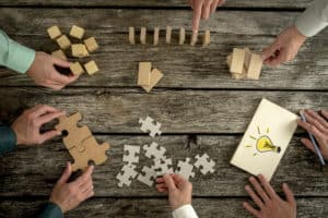 47284342 - businessmen planning business strategy while holding puzzle pieces, creating ideas with light bulb drawn on paper and rearranging wooden blocks. conceptual of teamwork, strategy, vision or education.